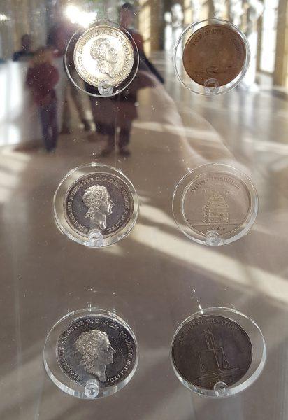 Szklane gabloty z monetami na wystawie w Starej Oranżerii